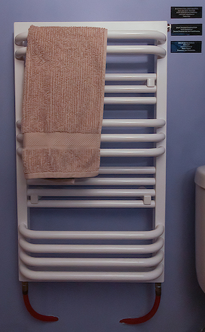 A towel hanging on a rack which is also a hot water radiator which heats the bathroom